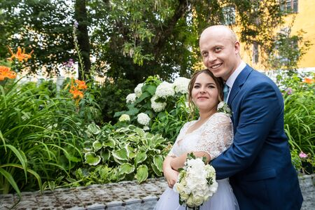 Russian bride and groom together in the green city park