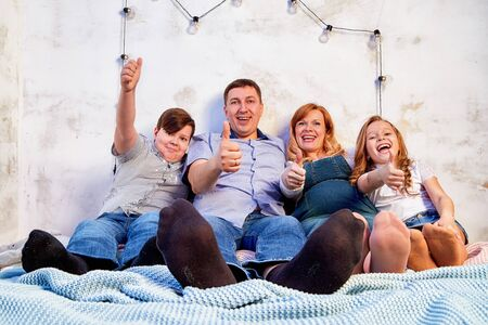 Family consisting mother, father, son, daughter spend time together and have fun at home in bed room