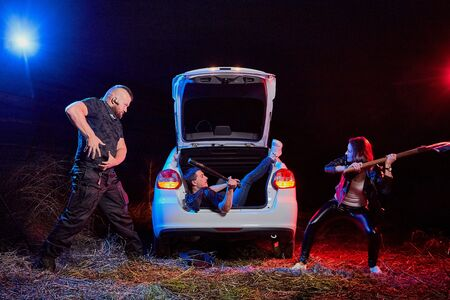 Couple of thugs near car trying to kill young guy in the trunk at night time and colored red and blue light around. Photoshoot about life of gungsters in Russia Reklamní fotografie