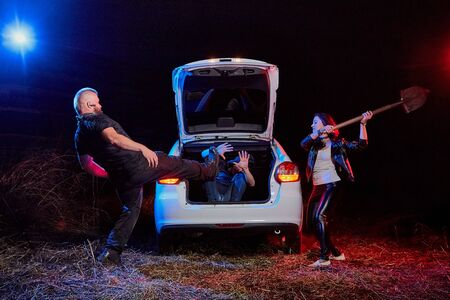 Couple of thugs near car trying to kill young guy in the trunk at night time and colored red and blue light around. Photoshoot about life of gungsters in Russia Foto de archivo