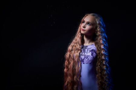Beautiful teen girl with long blonde curly hair in a dark room during photo shoot. Teenager young model during a photoshoot in photo studio 写真素材