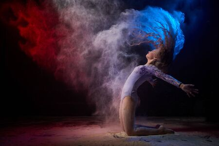 Beautiful teen girl with long blonde curly hair in a dark room with colored lights and clouds of flour. Sports teenager young model during a photoshoot with flying flour and color light Stock Photo