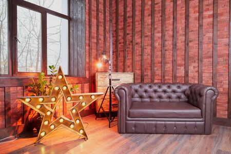 Interior of a living room with a sofa, window and and a shining star. Location for the photo shoot in red colour. Beautiful Living Room in Home