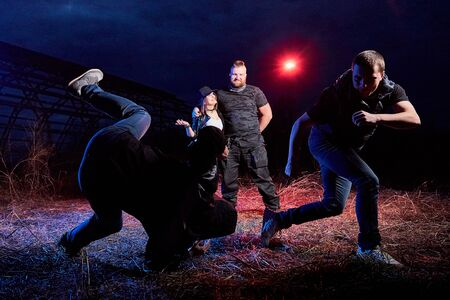 Fight four bandits in the field at night time and colored red and blue light around. Photoshoot about life of gungsters in Russia Imagens