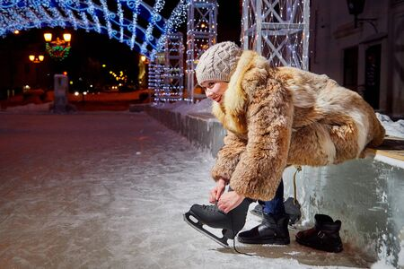 Girl with the skates at a public city rink with blue led light on a winter evening