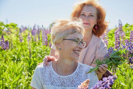 Deux amies dans le champ avec des fleurs violettes. Des femmes d'âge moyen potelées et minces retraitées se reposant dans un champ de lavande verte par une journée d'été ensoleillée. Deux soeurs en fleurs