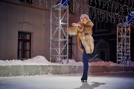 Girl skating on the ice arena in the evening city square in winter evening Stok Fotoğraf