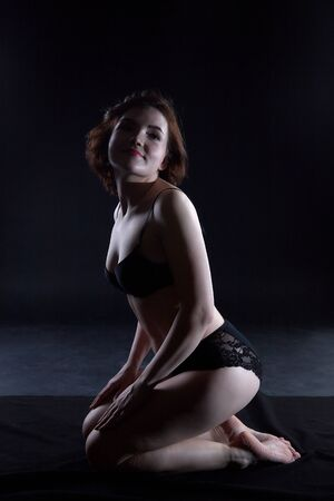 Sexy girl during professional photo shoot in dark room. Model in a black lingerie and erotic underwear. Black background