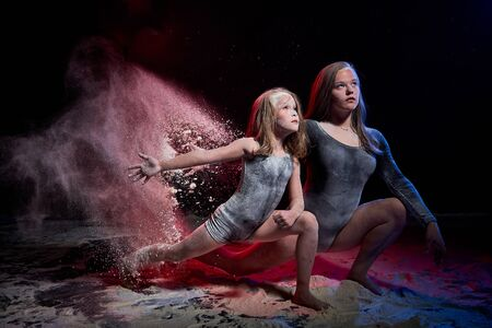 Two sisters in black studo with red and blue light during photoshoot with flour. Small girl and female tennager with white dust and emotion on the face and black background