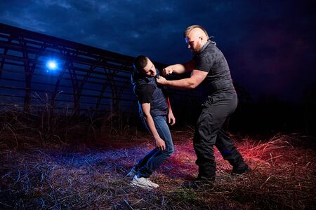 Fight of two men in the field at night time and colored red and blue light around. Special photoshoot about dangerous gangster life in Russia Stok Fotoğraf