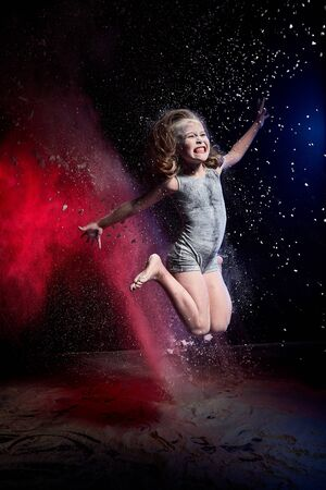 Small blonde girl jumping during photoshoot with flour in dark studio with colour red and blue light