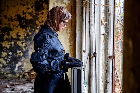 Girl in a black cloak, a scarf and a diplomat in an abandoned house near window. A spy in a secret meeting. Unusual photo shoot