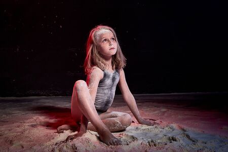 Small blonde girl during photoshoot with flour in dark studio 写真素材