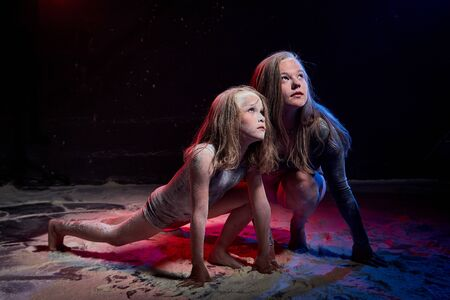 Two sisters in black studo with red and blue light during photoshoot with flour. Small girl and female tennager with white dust on the the face sitting on the floor