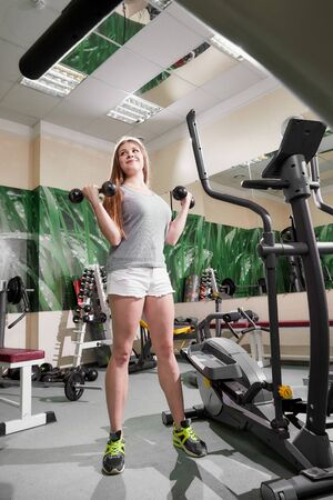 Attractive young woman in shorts and t-shirt working out with dumbbells at a gym. Model during photoshoot in gym in Russia