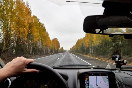 Track from the car window. Womans hand on the steering wheel. Female driver seeing autumn landscape during travel in auto Stock Photo