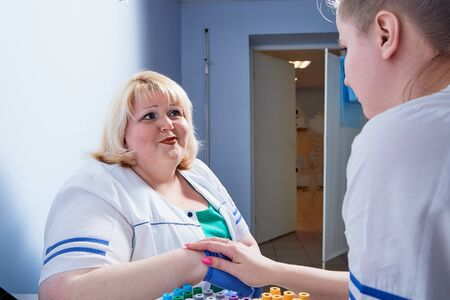 Experienced doctor fat woman and aspiring young doctor sittins at the table and discussing the medical problems at the hospital in Russia