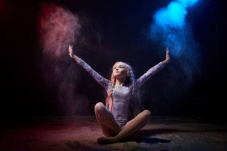 Beautiful teen girl with long blonde curly hair in a dark room with colored lights and clouds of flour. Sports teenager young model during a photoshoot with flying flour and color light 스톡 콘텐츠