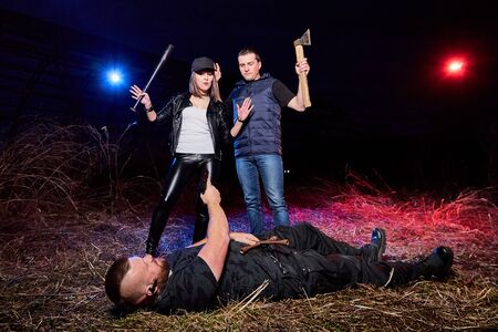 Two gangsters and brutal man in a field time and colored red and blue light around. Photoshoot about life of gungsters in Russia