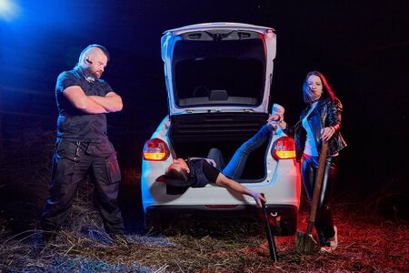 Couple of thugs near car and dead young guy in the trunk at night time and colored red and blue light around. Photoshoot about life of gungsters in Russia