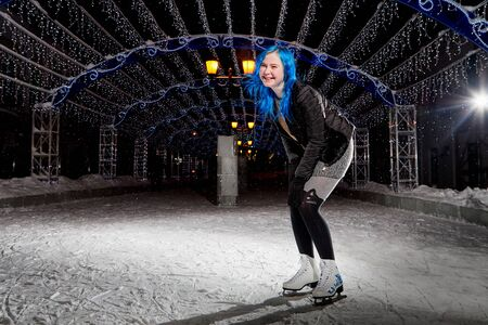 Girl wiht blue hair skating on the ice arena on the city square in winter evening