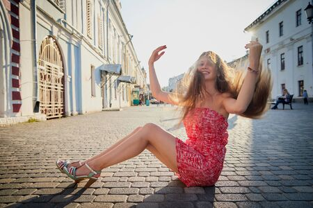 Brunette girl sitting on the cobblestones in the Central part of the old city in a sunny summer or spring day. Walk in downtown. Portrait of a funny pretty girl on paving stone of street of town Stock Photo