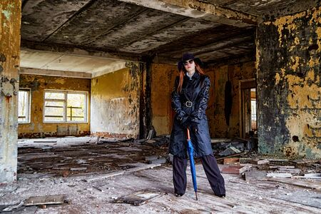 Girl in a black cloak and hat posing in an abandoned, ruined house. Unusual photoshoot