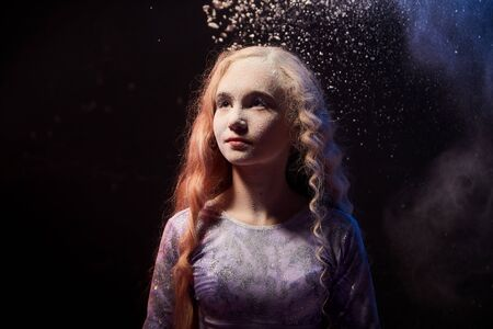 Beautiful teen girl with long blonde curly hair in a dark room with colored lights and clouds of flour. Sports teenager young model during a photoshoot with flying flour and color light 写真素材
