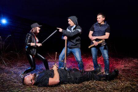 Trois bandits près d'un homme mort sur le terrain pendant la nuit et une lumière rouge et bleue colorée autour. Séance photo sur la vie des gangsters en Russie