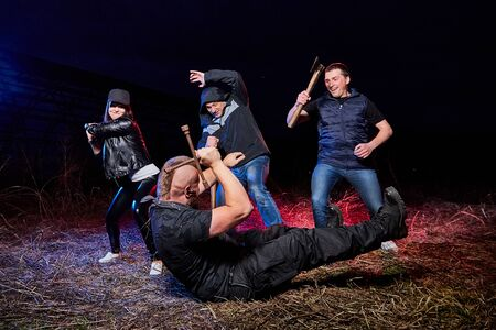 Fight four bandits in the field at night time and colored red and blue light around. Photoshoot about life of gungsters in Russia Foto de archivo