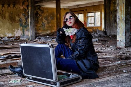 Girl in a black cloak with a diplomat and money in a ruined room. A spy in a secret meeting. Unusual photoshoot