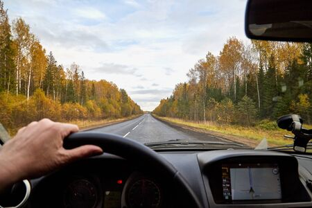 Track from the car window and white clouds on blue sky. Woman's hand on the steering wheel. Female driver seeing beautiful autumn landscape during travel in auto