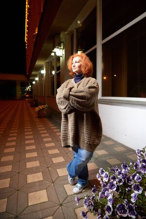 Middle-aged woman in a thick gray sweater on a city street at night. Elderly female pensioner in the evening and darkness with lights behind her Reklamní fotografie