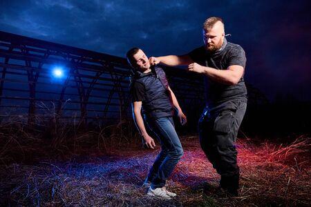 Combat de deux hommes sur le terrain la nuit et lumière colorée rouge et bleue autour. Séance photo spéciale sur la vie dangereuse des gangsters en Russie