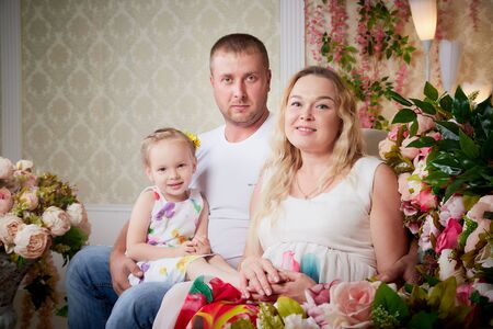 Family including father, pregnant mother and little daughter in a room with flowers. Dad, mom and little girl in a beautiful living room inside the house