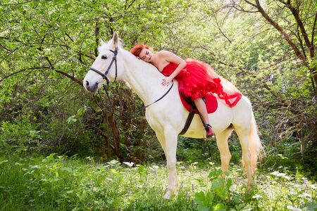 Girl in beautiful red dress on white horse in Park or forest. Photo shoot models and fashion. Unusual posing with an animal in the summer day on nature