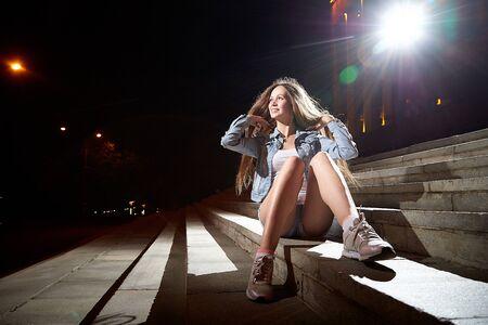 Joven hermosa mujer morena con el pelo largo en los escalones de las escaleras en una calle de la ciudad por la noche y luces de colores de flash cerca de ella