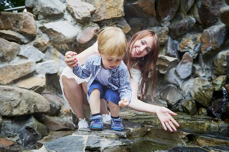 Cute baby blonde boy and his mother near grey rocks in a summer, spring or autumn day. Outdoor portrait Stock Photo