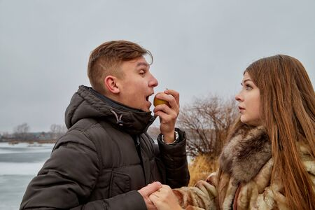 Romantic couple in love on autumn or winter walk near lake. Guy doesnt give an Apple to a girl