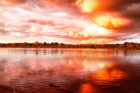 Sky with fantastic, amazing, stormy, disturbing red clouds over the river on a summer or autumn evening. Dramatic landscape with sky full of cloud at sunset