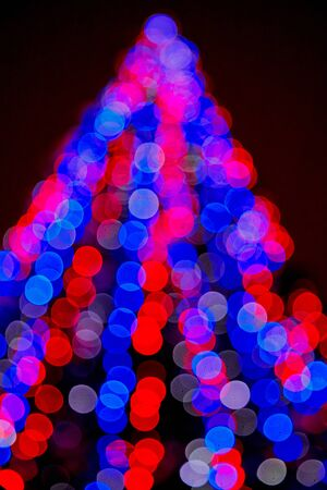 Abstract texture with light blue and red bokeh and black background in Christmas time. Christmas tree in blur