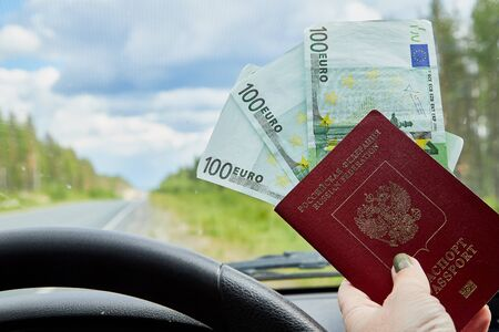 Euro banknotes and passport in a woman hand inside of a car and road with nature outside Фото со стока