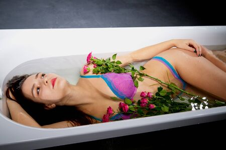 Young pretty brunette woman in bath with water and flowers. Model during an unusual photo shoot in a dark room