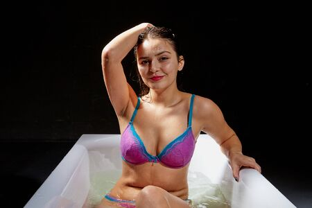 Young pretty brunette woman in bath with water and flowers. Model during an unusual photo shoot in a dark room 版權商用圖片 - 133295416