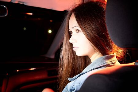 Beautiful young woman in the car at night with light background 版權商用圖片 - 133772909