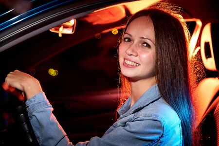 Beautiful young woman in the car at night with light background Reklamní fotografie