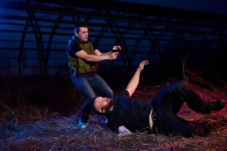 Soldier and instructor at night outdoors. A short man paratrooper and a large brutal male instructor during a military exercise dark night at the military training ground 版權商用圖片 - 133772917