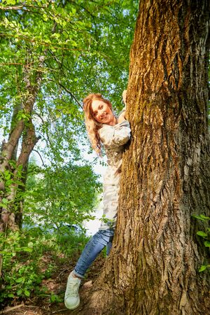 Beautirul girl with curly blonde hair near a tree in the park with sunny weather