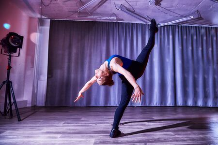 Flexible beautiful gymnast girl doing gymnastic exercises in the hall or on the stage. Young woman jumping in sport dress. Performance and posing actress or dancing model
