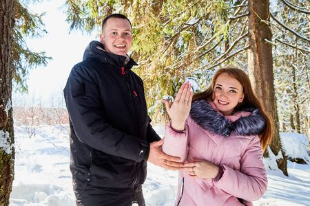 Marriage proposal. Guy gives engagement ring at red box to his girl in a winter forest